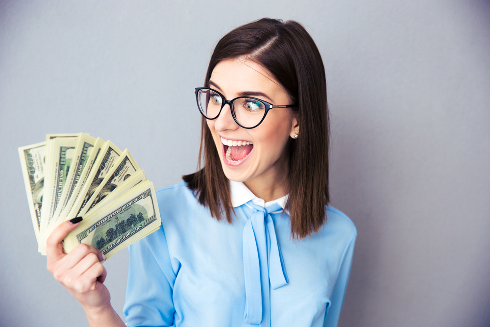 Cheerful businesswoman holding bills of dollar over gray background. Wearing in blue shirt and glasses.
