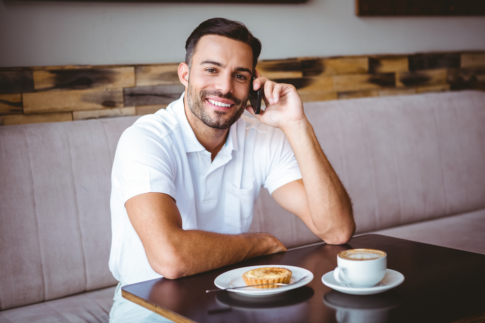 Portrait of young man smiling on the phone at the cafe