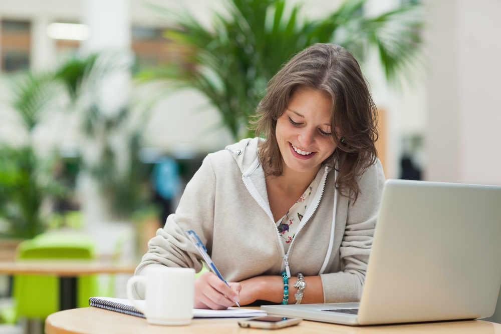 Smiling female student doing homework by laptop at cafeteria table